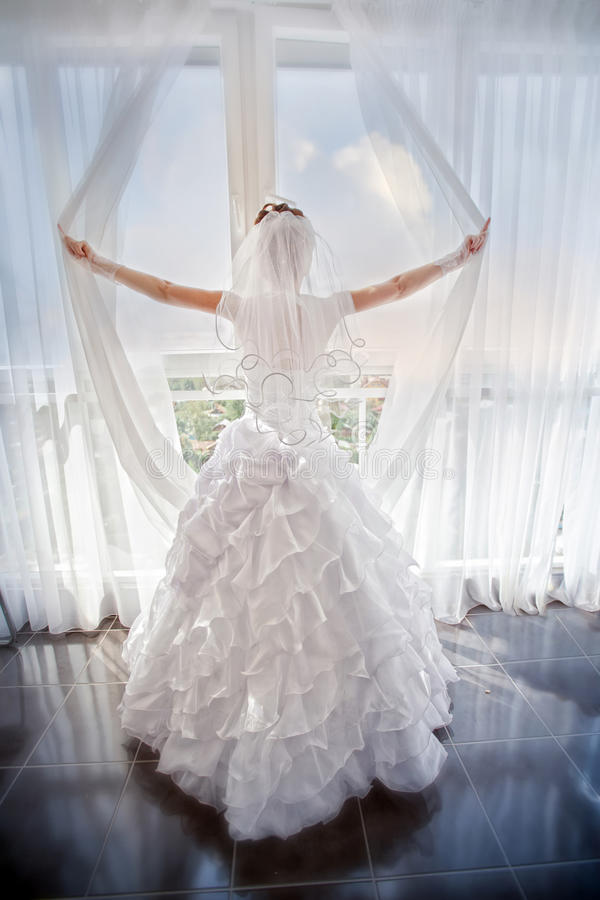 Braut nahe Fenster stockbild