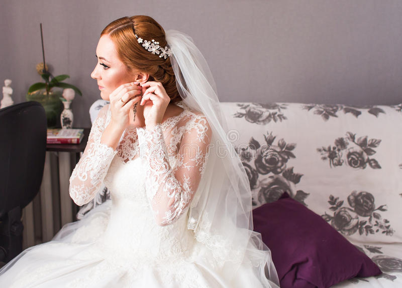 Braut nimmt die Ohrringe und heiratet Vorbereitung lizenzfreie stockfotografie
