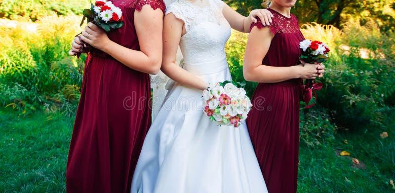 Braut, Reihe von Brautjungfern mit Blumensträußen an der großen Hochzeitszeremonie lizenzfreies stockbild