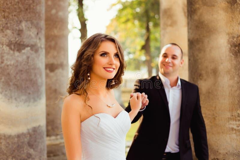 Braut schaut in der Luft, während Bräutigam ihre Finger zart hält lizenzfreie stockbilder