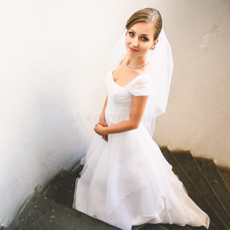 Braut schaut die schüchterne Aufstellung auf der Steintreppe stockbilder