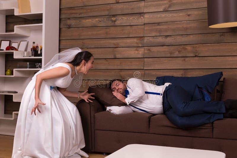 Braut schreit auf dem Schlafen auf Couchbräutigam lizenzfreie stockbilder