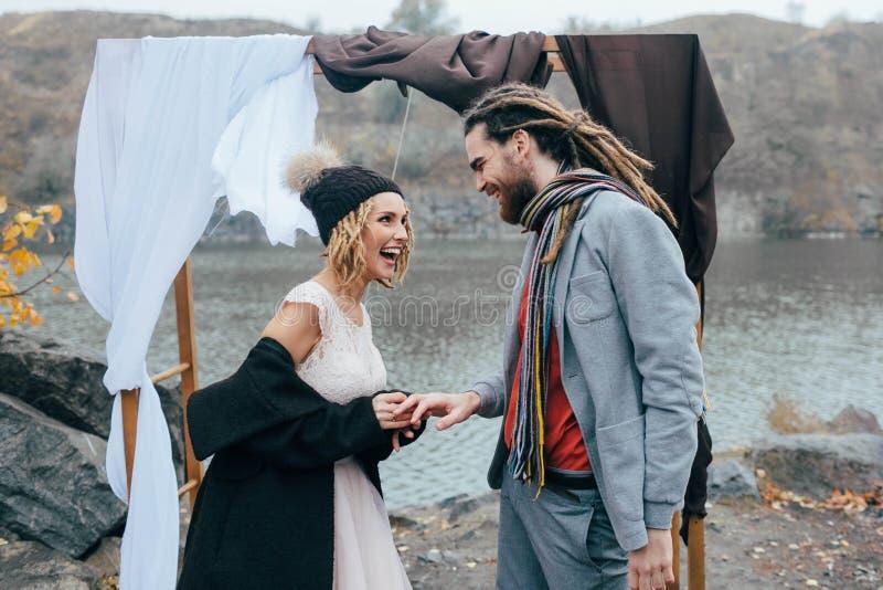 Braut setzt einen Ehering auf einen Bräutigam ` s Finger-, glücklichen und frohenmoment Herbsthochzeitszeremonie draußen lizenzfreie stockfotos