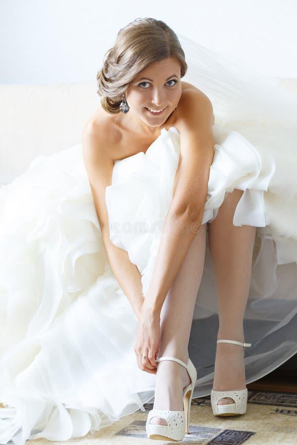 Braut setzt an Heiratsschuhe lizenzfreie stockfotos