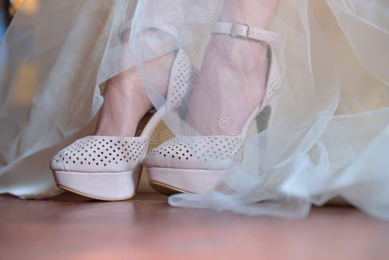 Braut setzt ihre Schuhe für die Heirat Spitze-Hochzeits-Kleid Morgenbr stockbild