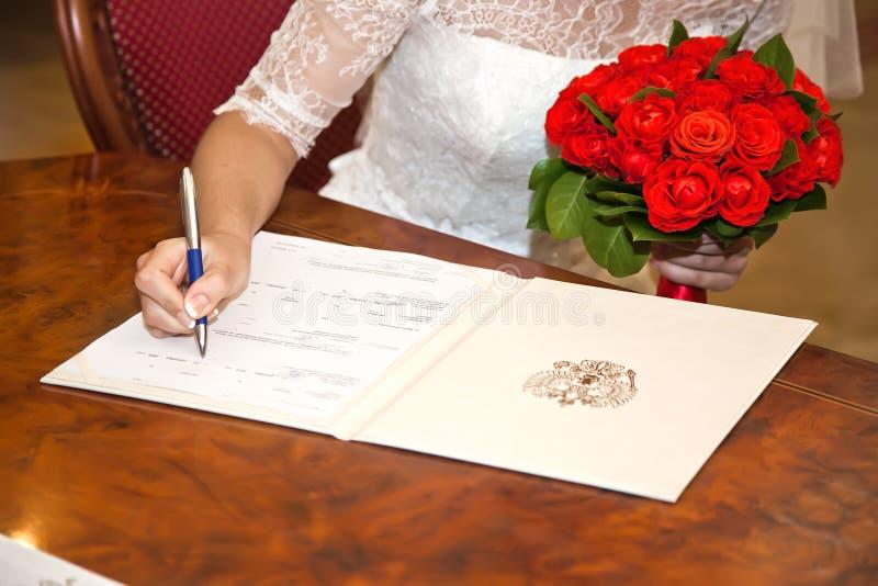 Braut setzt seine Unterschrift zur Dokument Heiratsurkunde lizenzfreie stockbilder