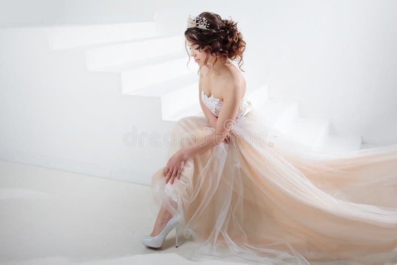 Braut sitzt auf der Treppe Porträt eines schönen Mädchens in einem Hochzeitskleid Tanzen-Braut, weißer Hintergrund stockfoto