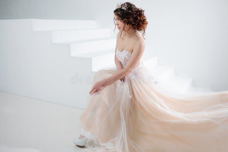 Braut sitzt auf der Treppe Porträt eines schönen Mädchens in einem Hochzeitskleid Tanzen-Braut, weißer Hintergrund stockbilder