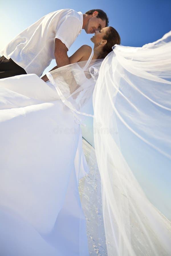 Braut-u. Bräutigam-Paar-Kuss an der Strand-Hochzeit lizenzfreie stockfotografie