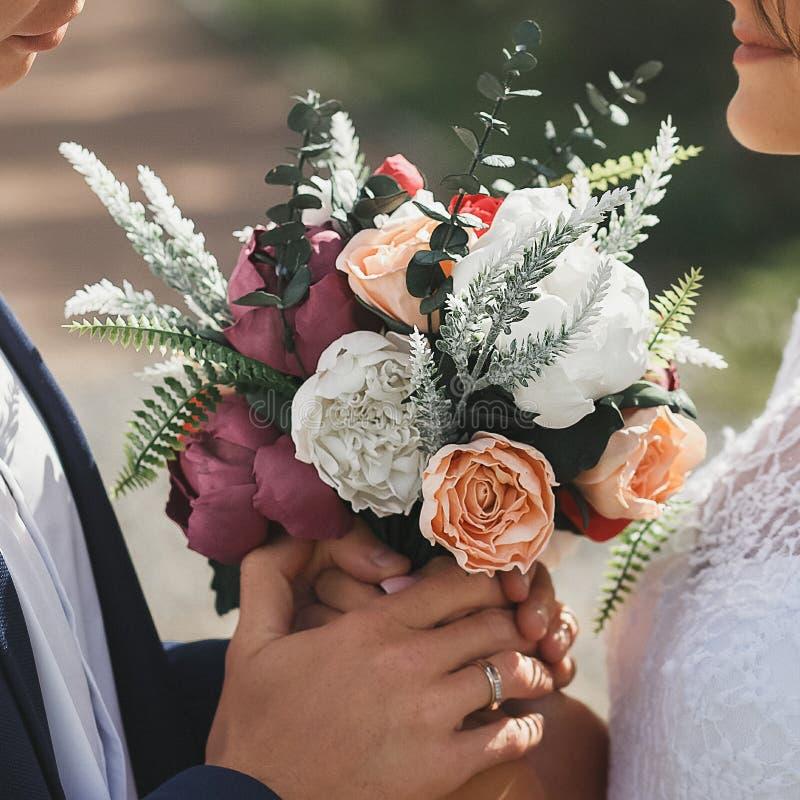 Braut und Bräutigam Holding Bridal Bouquet mit den Purpur-, sahnigen und weißenrosen draußen stockbild