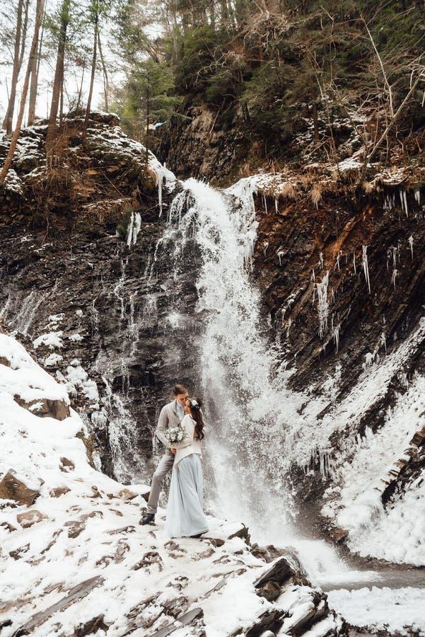 Braut und Bräutigam auf dem Gebirgswasserfall lizenzfreies stockfoto