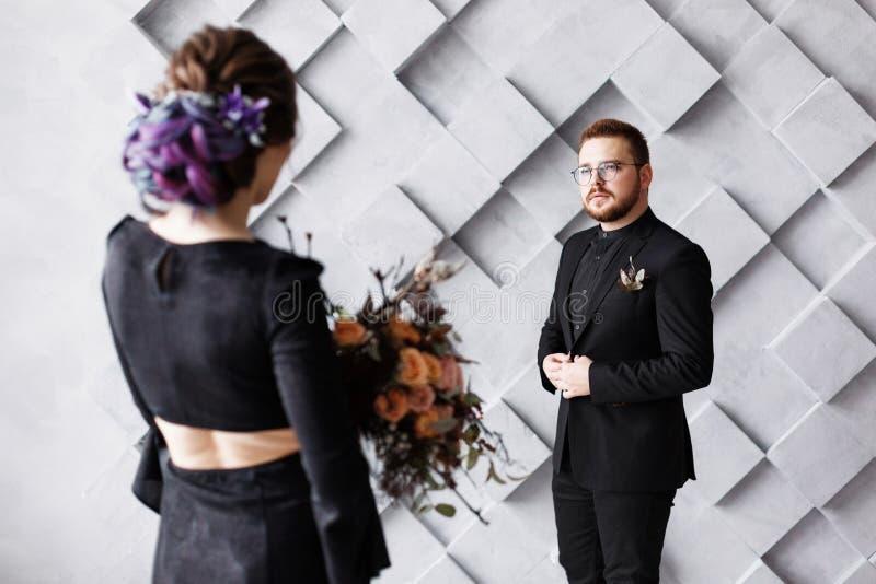 Braut und Bräutigam auf den grauen Quadraten des Hintergrundes im Studio Hintere Ansicht der Braut, Fokus auf Bräutigam Heiratend lizenzfreie stockfotos