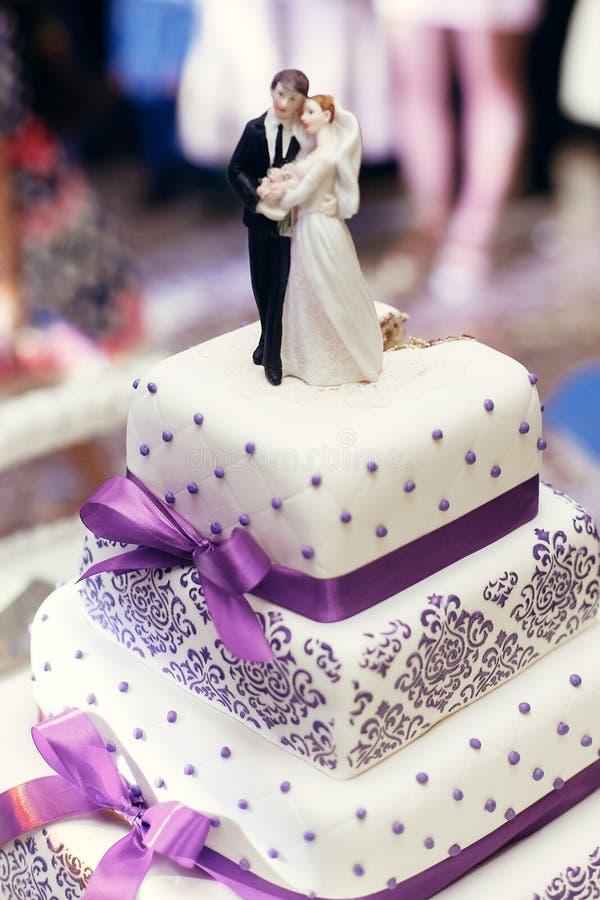 Braut und Bräutigam auf Hochzeitskuchen Figürchen auf die Kuchenoberseite mit purp stockbilder