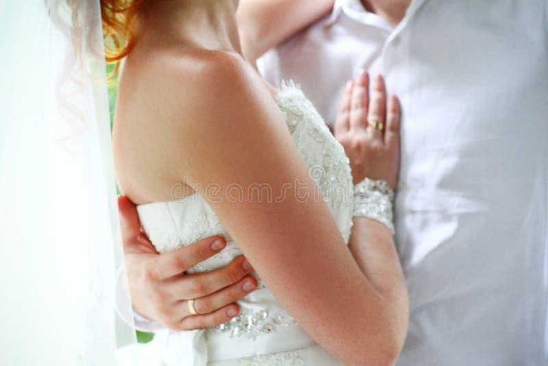 Braut und Bräutigam auf ihrem Hochzeitstagumarmen lizenzfreies stockbild