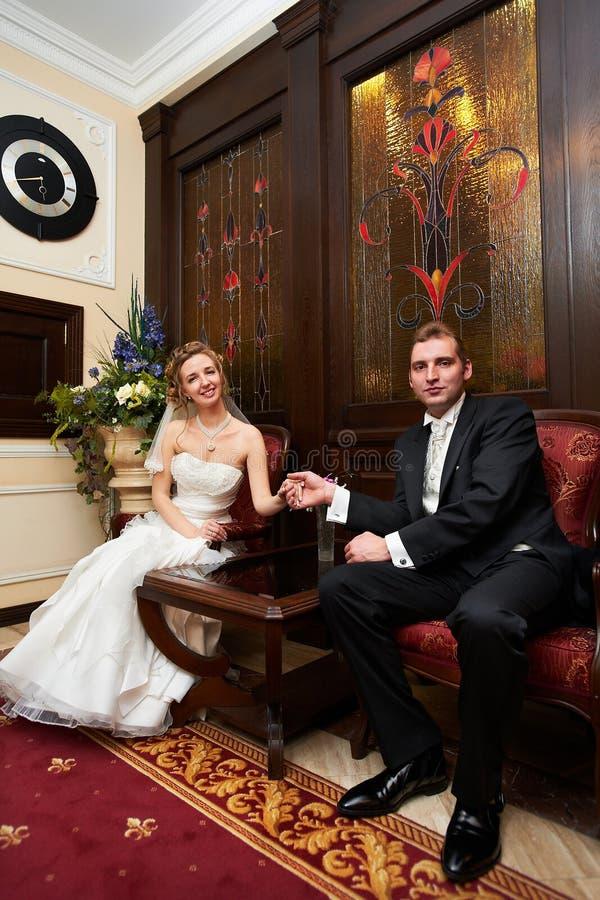 Braut und Bräutigam in den roten Stühlen lizenzfreie stockfotos