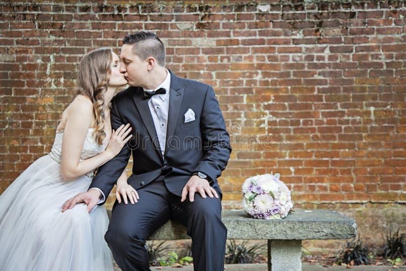 Braut und Bräutigam, die auf Bank vor Backsteinmauer sitzen stockfotografie