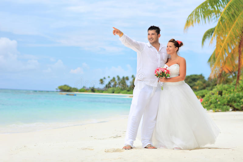 Braut und Bräutigam, die auf einem Strand umfassen lizenzfreie stockfotografie
