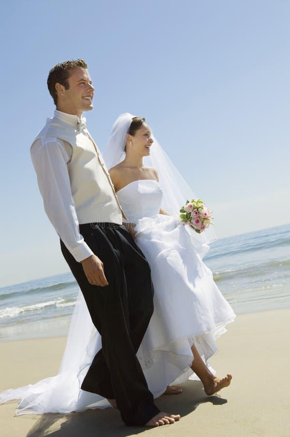 Braut und Bräutigam, die auf Strand gehen stockbild