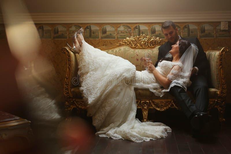 Braut und Bräutigam, die auf Weinlesesofa sitzen stockfotografie