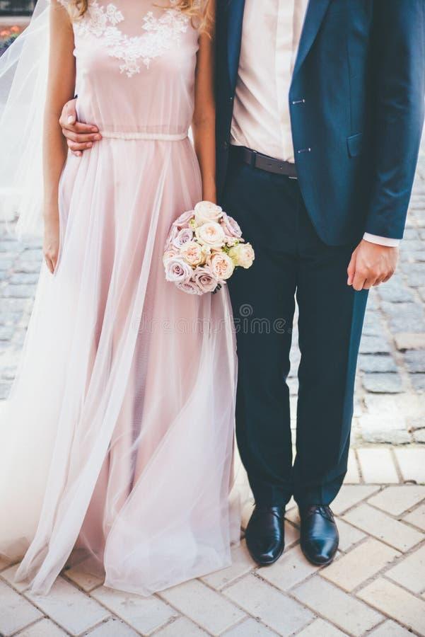 Braut und Bräutigam, die den rosafarbenen Blumenstrauß umarmen und halten lizenzfreie stockfotos