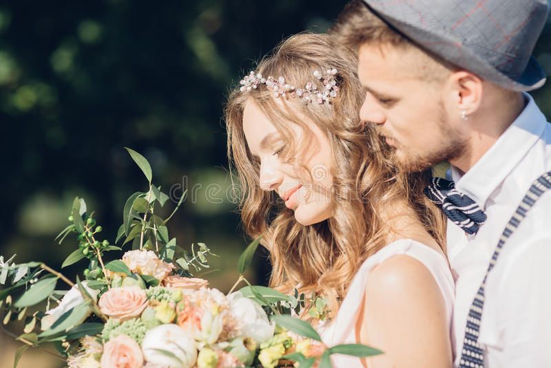 Braut und Bräutigam, die an der Hochzeit in der Natur umarmen lizenzfreies stockbild
