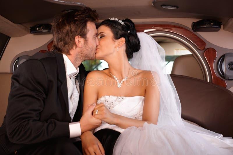 Braut und Bräutigam, die in der Limousine küssen lizenzfreies stockfoto