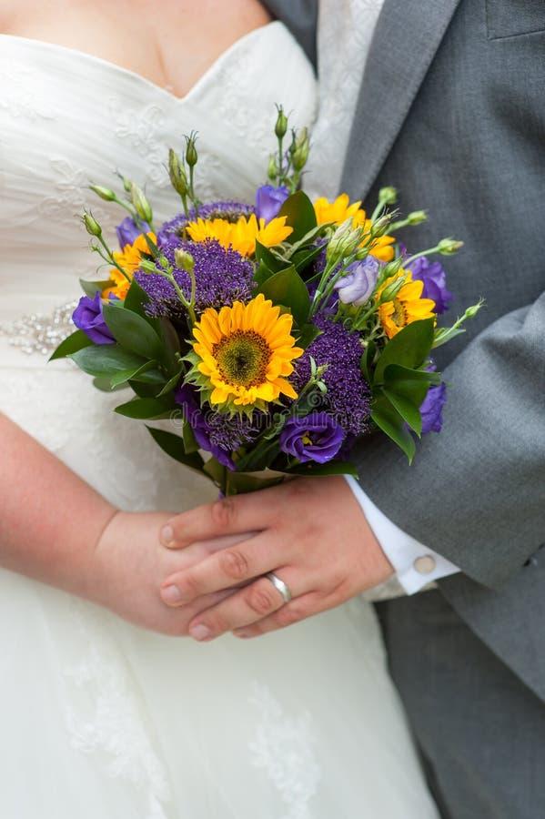 Braut und Bräutigam, die einen Hochzeitsblumenstrauß halten lizenzfreies stockfoto