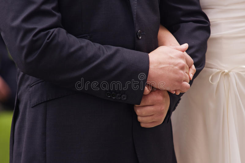Braut und Bräutigam, die ihre Hände anhalten stockfoto