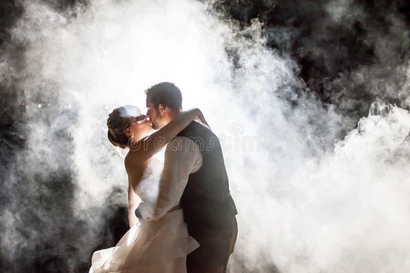 Braut und Bräutigam, die im Nebel nachts küssen lizenzfreie stockbilder