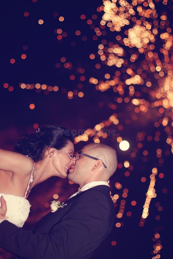 Braut und Bräutigam, die mit Feuerwerken im Hintergrund küssen stockfoto