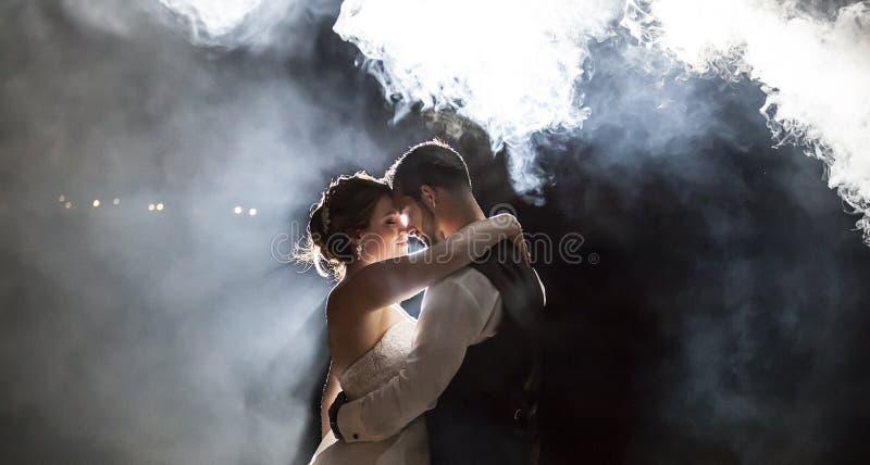 Braut und Bräutigam, die unter Nebel nachts küssen lizenzfreies stockbild