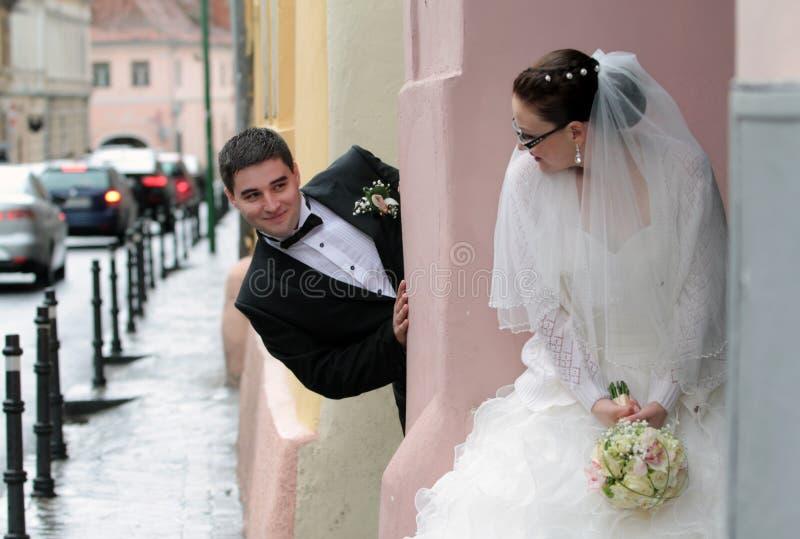 Braut und Bräutigam, die Verstecken spielen lizenzfreie stockfotos