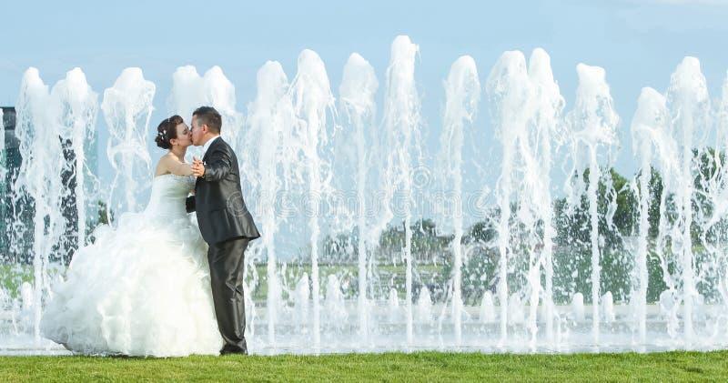 Braut und Bräutigam, die vor Wasserspraybrunnen küssen stockfoto