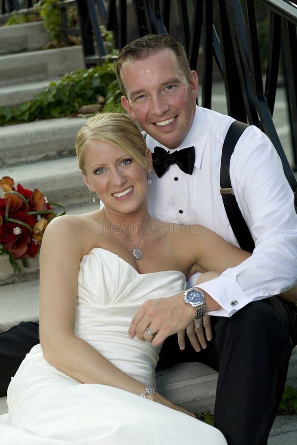 Braut und Bräutigam, die zusammen sitzen stockbild