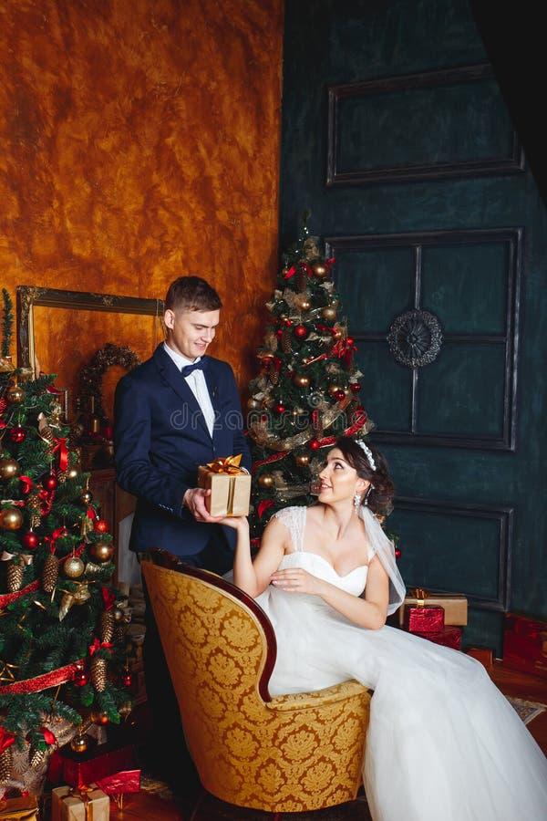 Braut und Bräutigam draußen Liebhaber Braut und Bräutigam in der Weihnachtsdekoration Bräutigam, der Geschenk hält Romantische Üb stockbilder