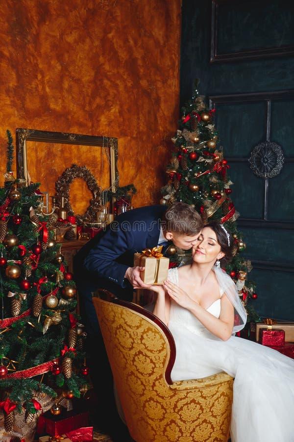 Braut und Bräutigam draußen Liebhaber Braut und Bräutigam in der Weihnachtsdekoration Bräutigam, der Geschenk hält Romantische Üb lizenzfreie stockfotografie