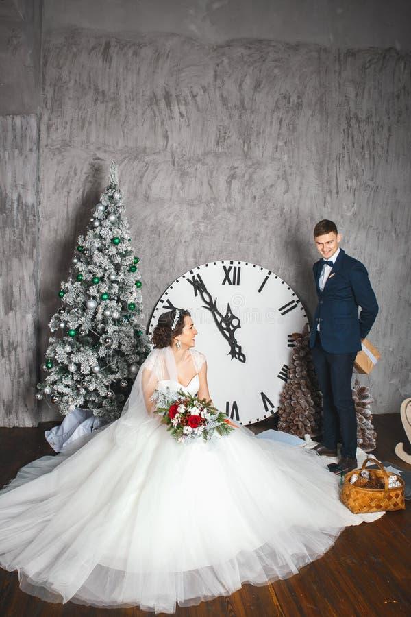 Braut und Bräutigam draußen Liebhaber Braut und Bräutigam in der Weihnachtsdekoration Bräutigam, der Geschenk hält Romantische Üb stockfoto