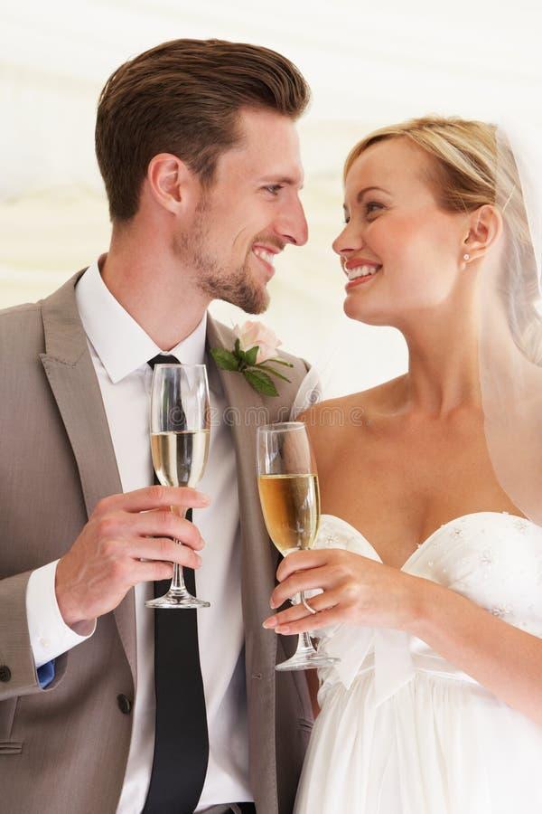 Braut und Bräutigam Drinking Champagne At Wedding stockbild