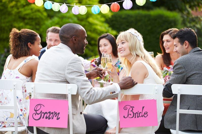 Braut-und Bräutigam-Enjoying Meal At-Hochzeitsempfang stockbild