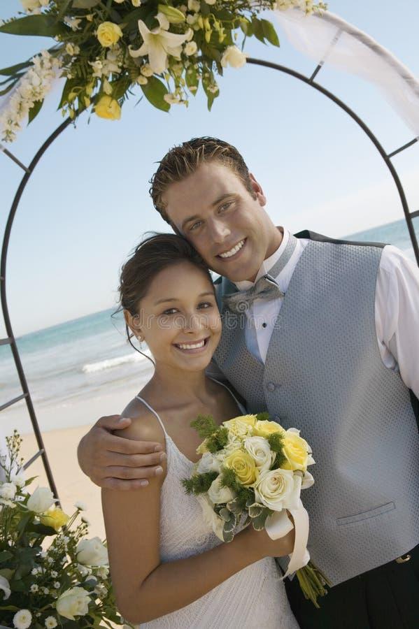 Braut und Bräutigam With Flower Bouquet auf Strand lizenzfreies stockfoto