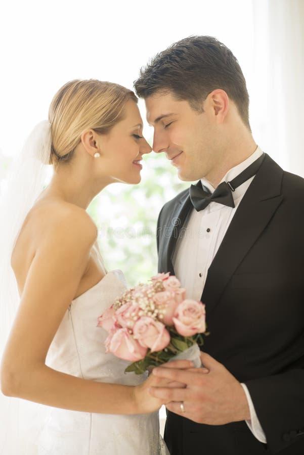 Braut-und Bräutigam-With Flower Bouquet-Reibungs-Nasen stockfotos