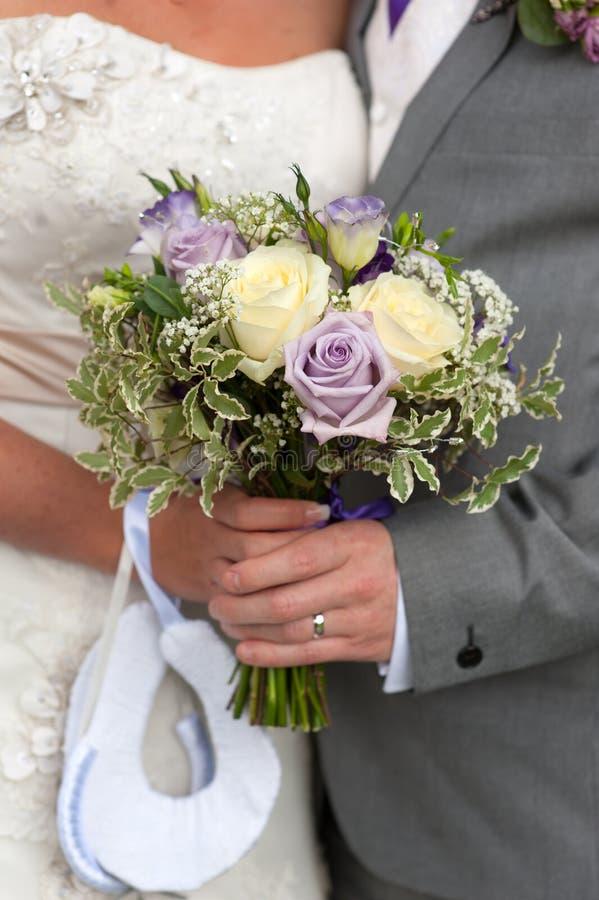 Braut und Bräutigam halten einen Hochzeitsblumenstrauß stockbilder