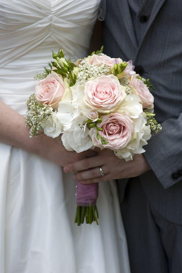 Braut und Bräutigam halten Hochzeitsblumenstrauß an lizenzfreies stockbild