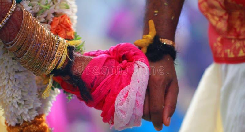 Braut und Bräutigam Hands Together an einer indischen Hochzeits-Zeremonie lizenzfreies stockbild