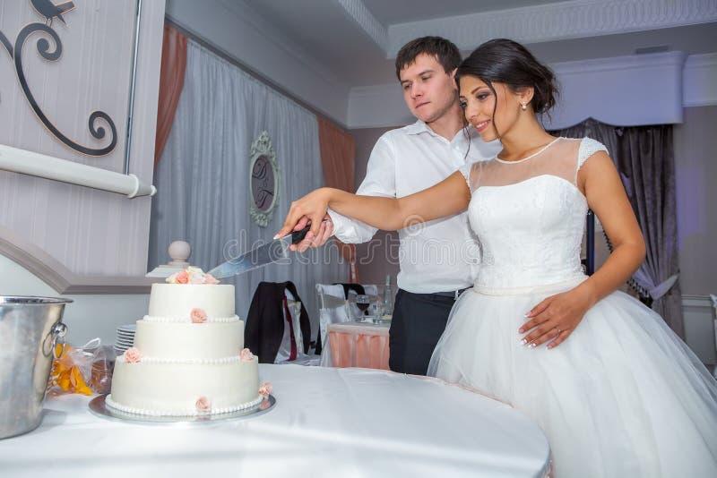 Braut und Bräutigam am Hochzeitsempfang, der die Hochzeitstorte schneidet stockfotografie