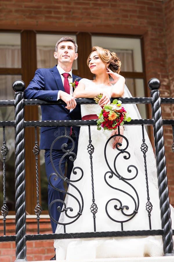 Braut und Bräutigam am Hochzeitstag draußen gehend Glückliche Jungvermähltenumfassung Liebevolle Paare stockfotos