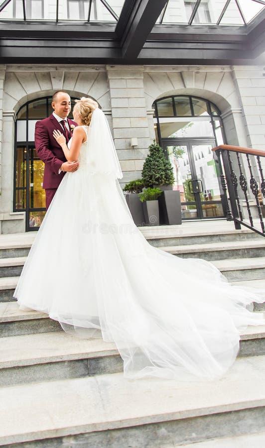 Braut und Bräutigam am Hochzeitstag draußen gehend Glückliche Jungvermähltenumfassung Liebevolle Paare stockfoto