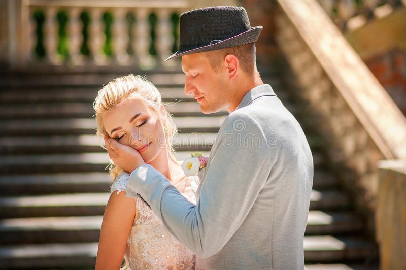 Braut und Bräutigam im Sommer Liebendes Ehepaar in der Stadt Dnipro, Ukraine Hut Nahkuss und Gebot stockfotos