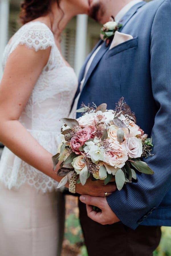 Braut und Bräutigam Kiss Hochzeitsblumenstrauß toge halten lizenzfreie stockbilder