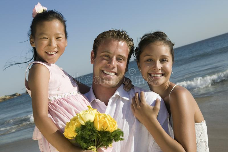 Braut und Bräutigam mit Blumenmädchen am Strand lizenzfreie stockbilder